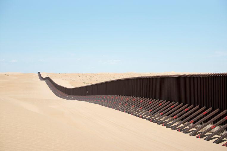 Een stuk grensmuur doorkruist de woestijn, ten oosten van Calexico, Californië. Beeld Getty Images