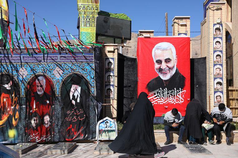 Bezoekers van het graf van de vorig jaar gedode Iraanse generaal Qassem Soleimani (op de poster) in Kerman, Iran. (02/01/2021) Beeld VIA REUTERS