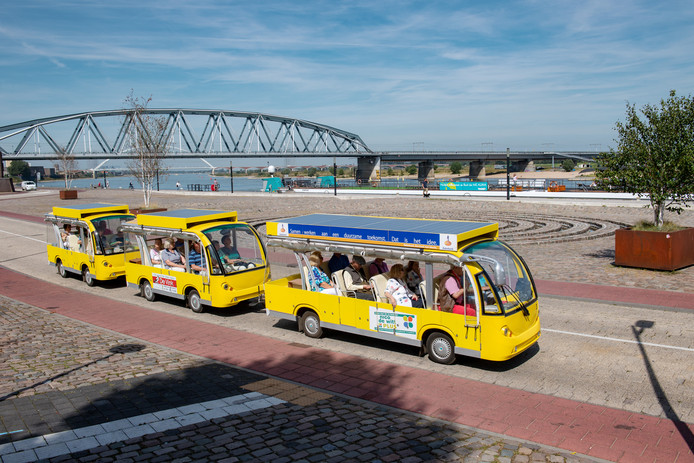 De Ooijse zonnetrein op de Waalkade in Nijmegen, vol toeristen van een Duits cruiseschip.