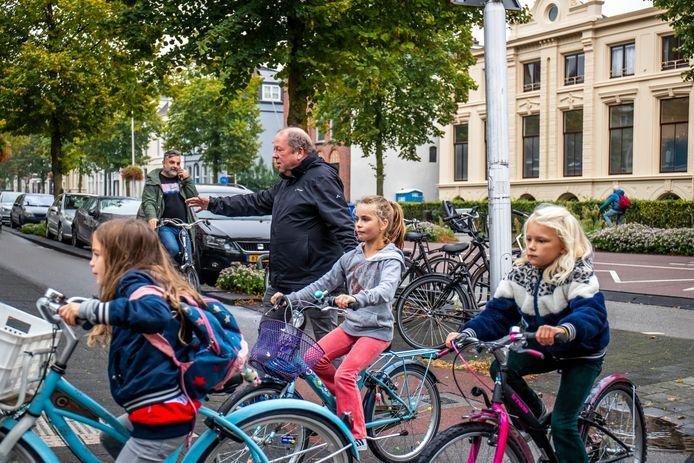 Schooldirecteur Jaap Nelissen tussen zijn leerlingen op de hoek waar tot voor kort anti-abortus demonstraties plaatsvonden. Schuin tegenover, de abortuskliniek.