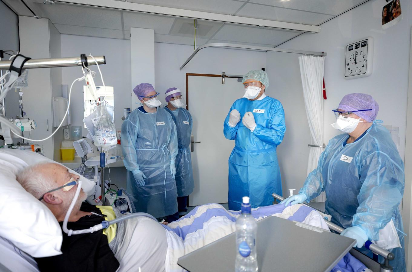Koning Willem-Alexander (m) bezoekt in beschermende kleding een afdeling met covidpatienten in het Van Weel-Bethseda Ziekenhuis in Dirksland.
