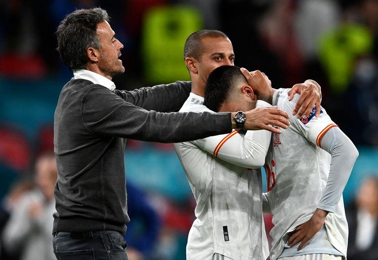 De geëmotioneerde Pedri wordt na de verloren strafschoppenserie getroost door Thiago en bondscoach Luis Enrique.  Beeld AP
