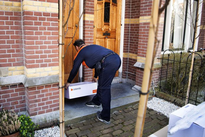 Een postbezorger doet een contactloze bezorging.