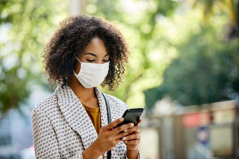 Businesswoman using smart phone in city. Entrepreneur is looking at cell while standing outdoors during pandemic. She is in formals. Beeld Getty Images