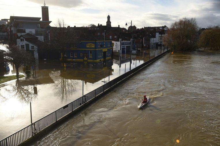 Storm Christoph heeft in het noordwesten van Engeland voor hevige regenval en overstromingen gezorgd. In Shrewsbury kon er zelfs vlak langs het centrum gekayakt worden. De rivier Severn, rechts, ligt normaal een paar meter lager. Beeld AFP