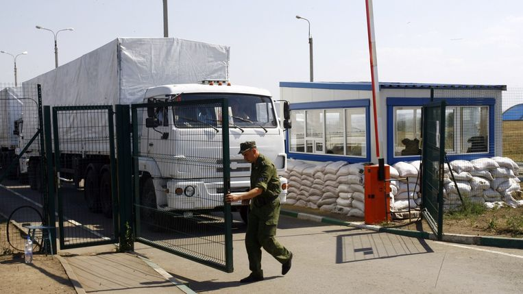 Een grenswacht laat de Russische vrachtwagens door. Volgens een woordvoerder van het Oekraïense leger zijn 90 vrachtwagens de grens overgegaan. Rusland zou daarmee de afspraken met Oekraïne hebben geschonden. Beeld afp