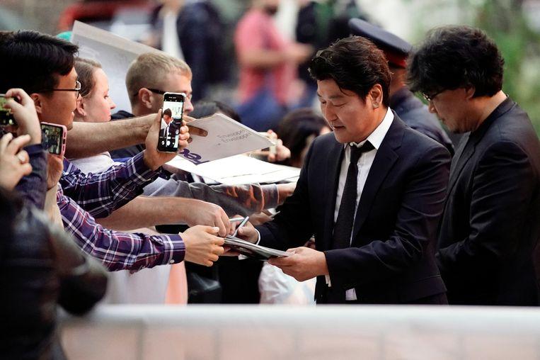 Acteur Song Kang-Ho (links) en regisseur Bong Joon-ho delen handtekeningen uit op het filmfestival in Toronto. Beeld REUTERS
