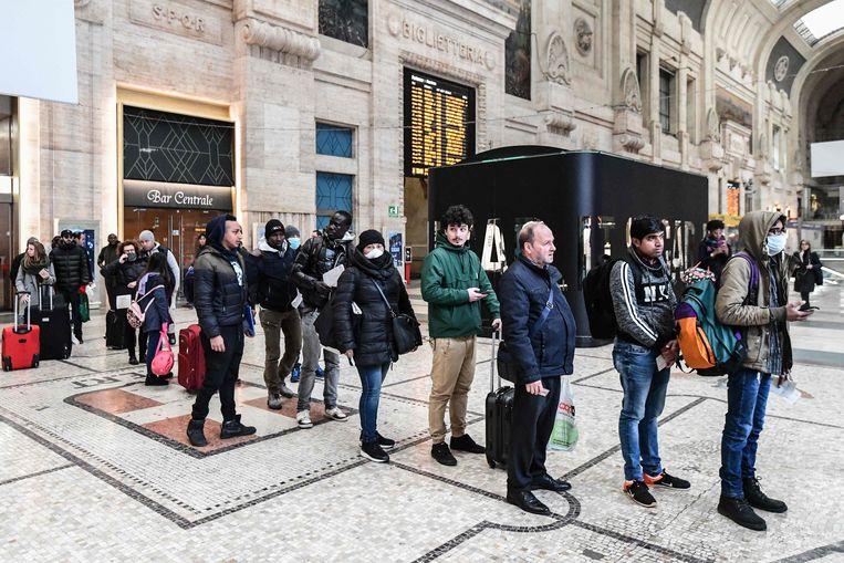 Passagiers maandag in de rij op het station van Milaan. Ze worden gecontroleerd voor ze aan boord mogen. Beeld AFP