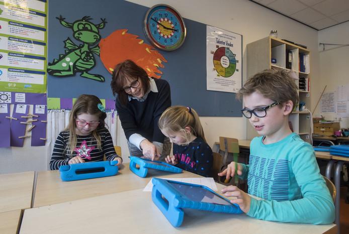 Nina, Myrthe en Daan (vlnr) en juf Irna Nieterau van groep 4a van basisschool De Rank werken in de klas op iPads.