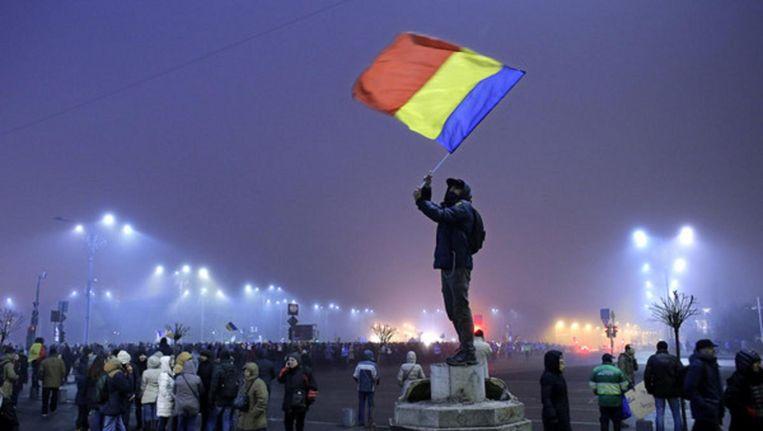 Roemeense jongeman zwaait met de nationale vlag in een demonstratie voor de regeringsgebouwen, 6 februari. Beeld epa