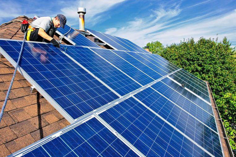 Een arbeider installeert zonnepanelen op een dak. Beeld ThinkStock