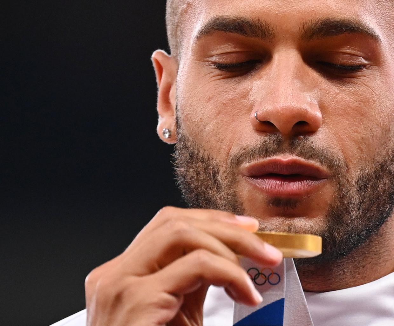 Lamont Marcell Jacobs  met zijn gouden medaille. Beeld Reuters
