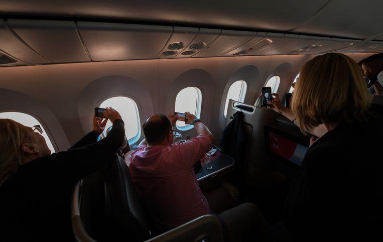 Passagiers nemen foto's tijdens een van de 'vluchten naar nergens' die Qantas vorig jaar uitvoerde langs een reeks Australische bezienswaardigheden. Beeld Getty Images
