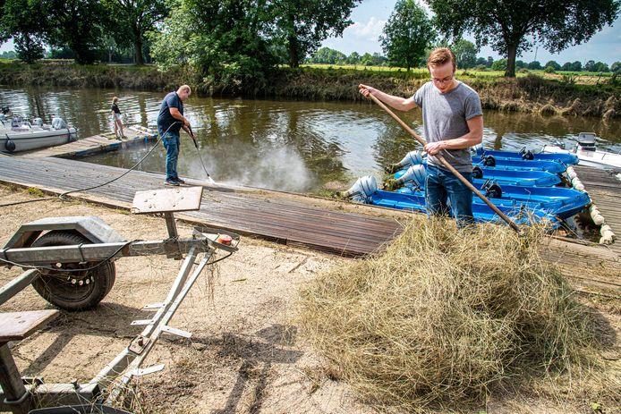 Aaron Vuurman (met hogedrukspuit) is met zijn personeel druk bezig om de rommel op te ruimen. Het Maaswater liet vooral veel hooi achter.