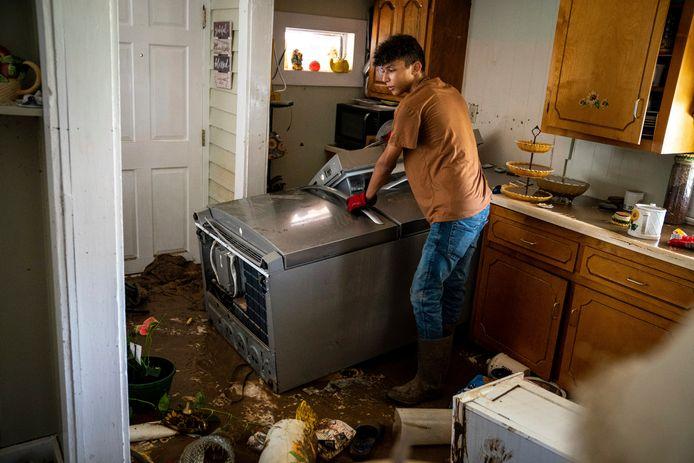 Een jongen helpt een beschadigde keuken te ontruimen in Tennessee.