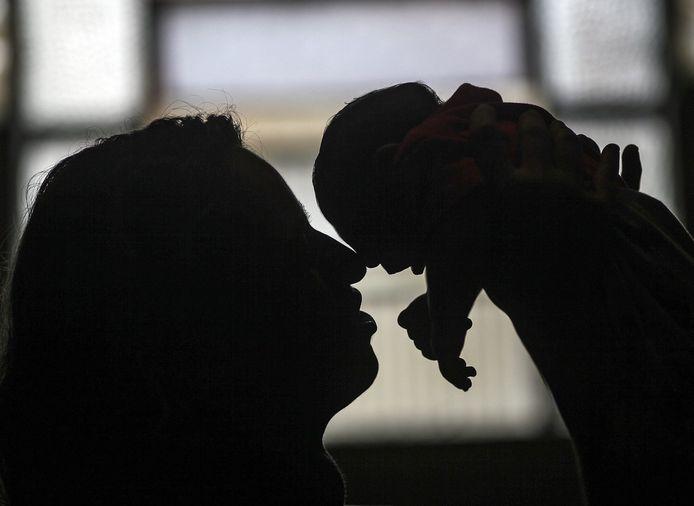 Een vrouw houdt haar kleindochter vast. Het kindje lijdt aan microcefalie, een mogelijk gevolg van het zikavirus dat haar moeder opliep.