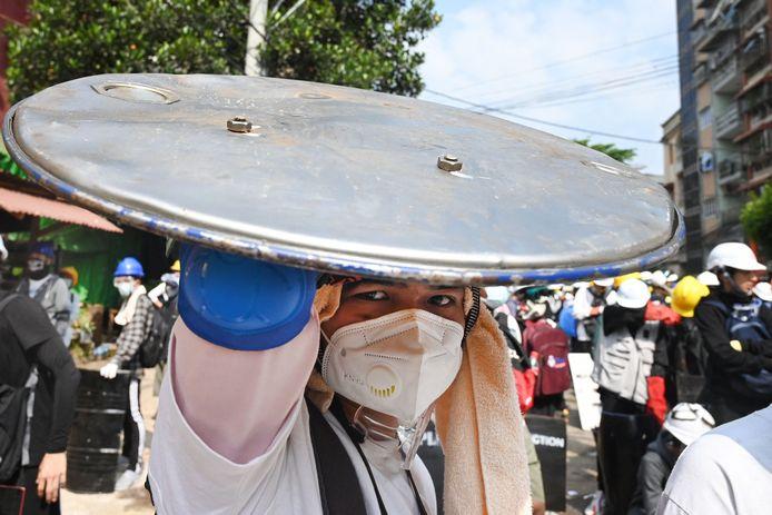 Een demonstrant in Yangon gebruikt een deksel van een vuilnisbak als geïmproviseerd schild.