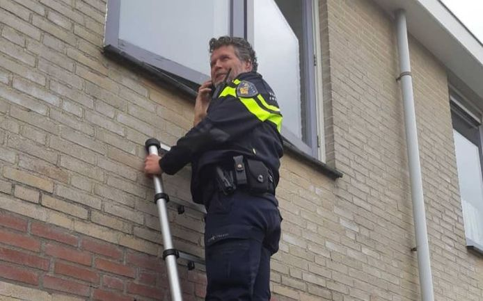 Een agent neemt een kijkje door het raam op de eerste etage.