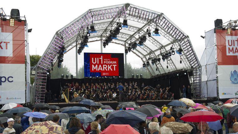 Drukte en paraplu's zaterdag op de Uitmarkt in Amsterdam bij een uitvoering van Radio Filharmonie en groot omroepkoor. © ANP Beeld