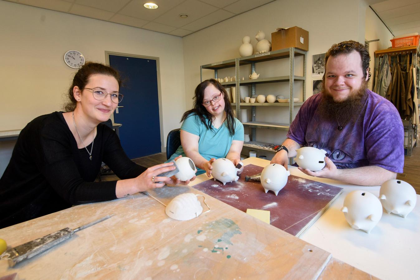 Mark Bakker en Jamie van der Hamsvoort bezig met het afwerken van net gebakken kleiproducten onder toeziend oog van begeleidster Hanneke Sõntjens.