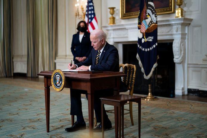 Joe Biden ondertekent een decreet, achter hem staat vicepresident Kamala Harris.