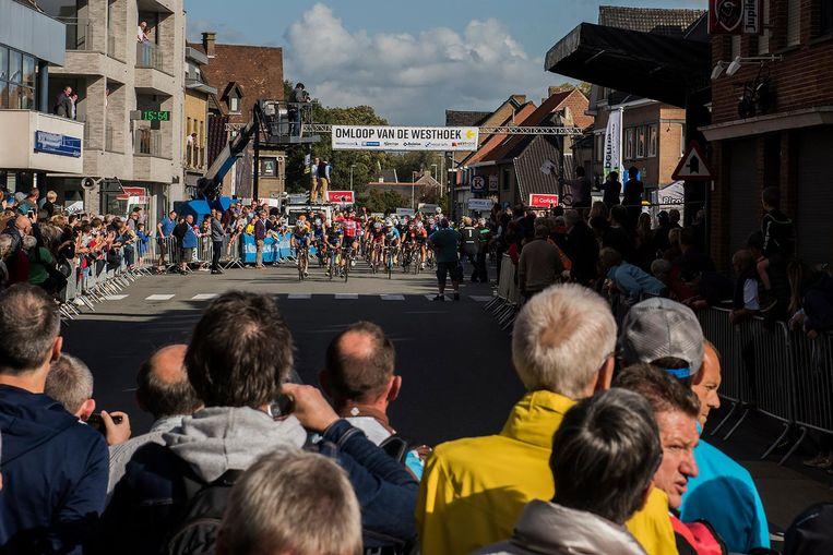 De wielersupporters kijken toe hoe sprinter André Greipel al juichend over de meet rijdt.