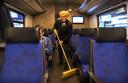 Foto ter illustratie. Een schoonmaker haalt een bezem door de trein op station Den Haag Centraal.