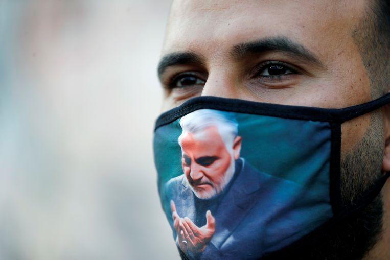 Mondkapje met de beeltenis van Qassem Soleimani. Gisteren was het een jaar geleden dat  de Iraanse generaal van de Revolutionaire Garde met een raketaanval werd geliquideerd door  de Verenigde Staten. In Bagdad wordt zijn dood de hele week herdacht. Beeld REUTERS