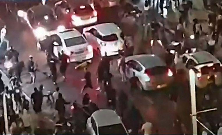 Een still van de live-utizending van nieuwszender Kan News waarop te zien is hoe een vermoedelijk Arabische man uit een auto wordt getrokken en mishandeld.  Beeld AFP