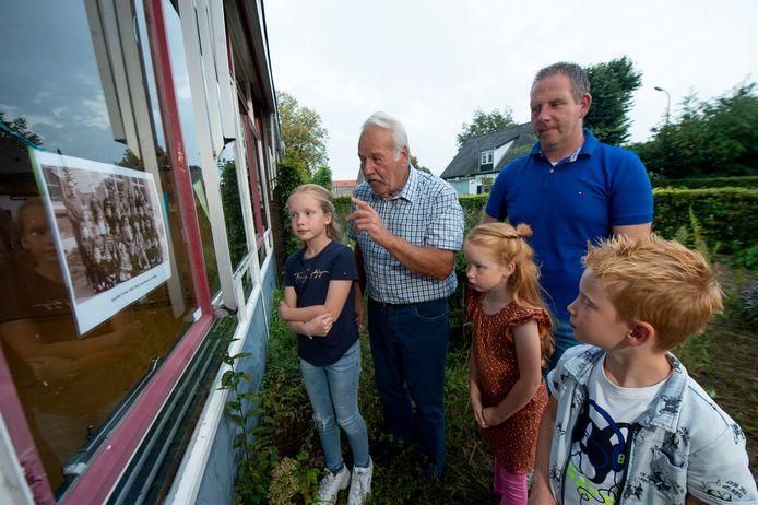 Demi, Quinty, Levi (vlnr) en hun vader Remco luisteren aandacht als opa Jan vertelt.
