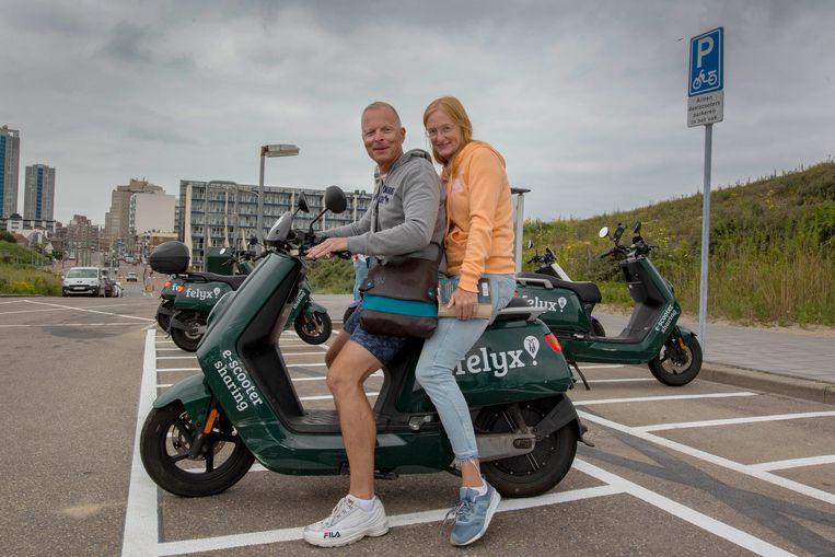 Duitse toeristen Tanja Jochum & Stefan Voellmer, verbaasden zich erover dat ze geen helm hoeven te dragen als ze de deelscooter gebruiken.  Beeld Maartje Geels