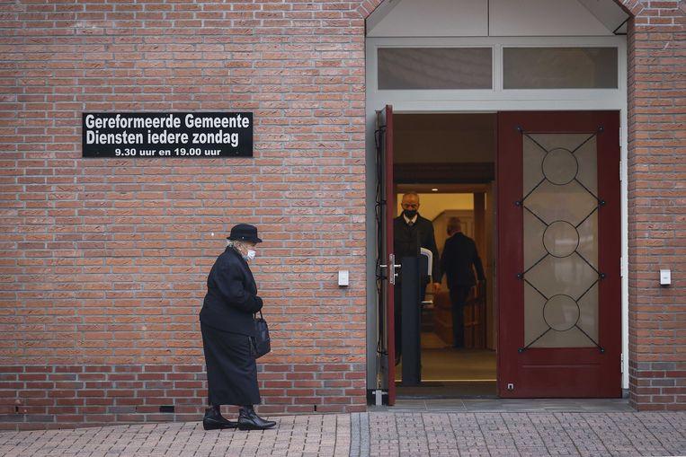 Kerkgangers komen aan bij de Rehobothkerk in Barneveld voor de wekelijkse kerkdienst. Beeld ANP