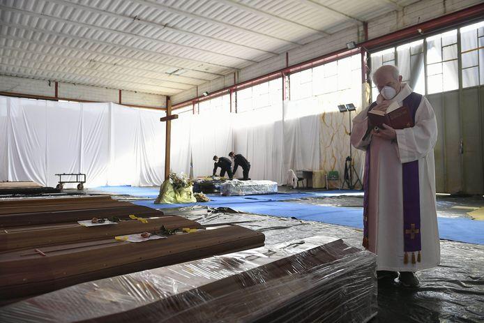 Ponte San Pietro (Bergame), le 13 avril 2020. Un prêtre bénit les cercueils des défunts alignés dans des hangars, faute de place dans les funérariums