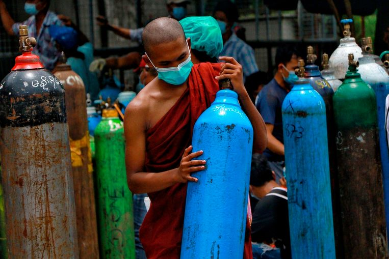 Een boeddhistische monnik houdt een zuurstoffles vast. In Myanmar stierven vorige week minstens 2.500 personen aan covid-19. De chaos in de ziekenhuizen is groot sinds de coup in februari, aan vrijwel alles is een tekort.   Beeld AP