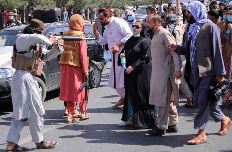 Een Talibanstrijder richt zijn geweer dinsdag op betogers tijdens een protest. Beeld REUTERS