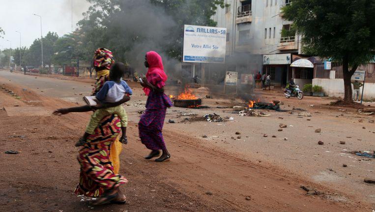 Vrouwen lopen met een kind langs rokende autobanden na een demonstratie in de Malinese hoofdstad Mali. Beeld AP