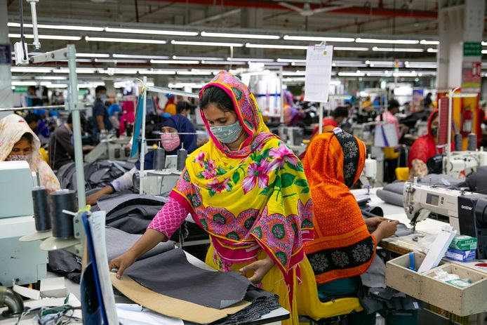 In landen als Vietnam en Cambodja gaan sommige textielfabrieken dicht door de nieuwe lockdown, dat is in deze fabriek in Dhaka (Bangladesh) nog niet het geval. De regering heeft besloten dat de bedrijven ondanks de lockdown open mogen blijven.