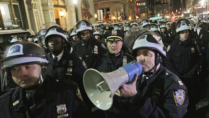 Een politieman roept Occupy-betogers op hun kampement in het New Yorkse Zuccotti Park te verlaten, vorige week dinsdag.