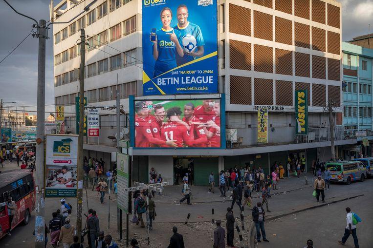 Een billboard in de straten van Nairobi probeert nieuwe spelers te lokken. Beeld Sven Torfinn/Panos Pictures