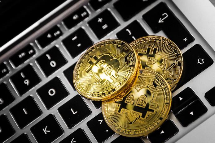Een laptop en de cryptovaluta Bitcoin. Veel mensen zien de digitale munt als investering terwijl economen waarschuwen voor een bubbel.