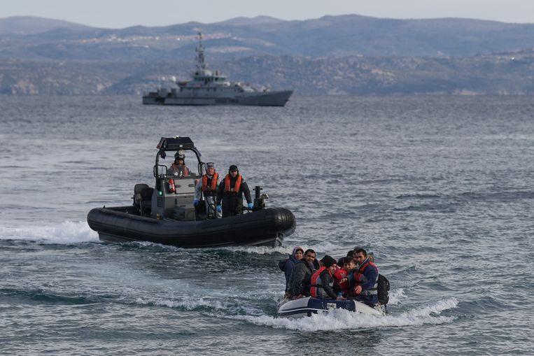 Een bootje met 15 Afghaanse vluchtelingen vaart naar het Griekse Lesbos. Achter hen een patrouilleboot van Frontex.  Beeld Hollandse Hoogte / AFP