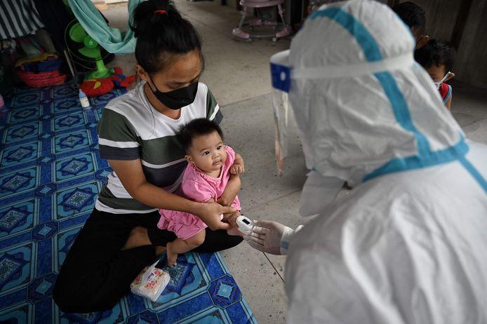 Een gezondheidswerker checkt de zuurstofwaarde in het bloed bij een kindje in de omgeving van Bangkok.