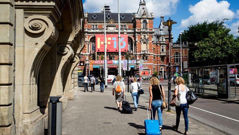 Toeristen met rolkoffers op het Leidseplein in Amsterdam Beeld anp