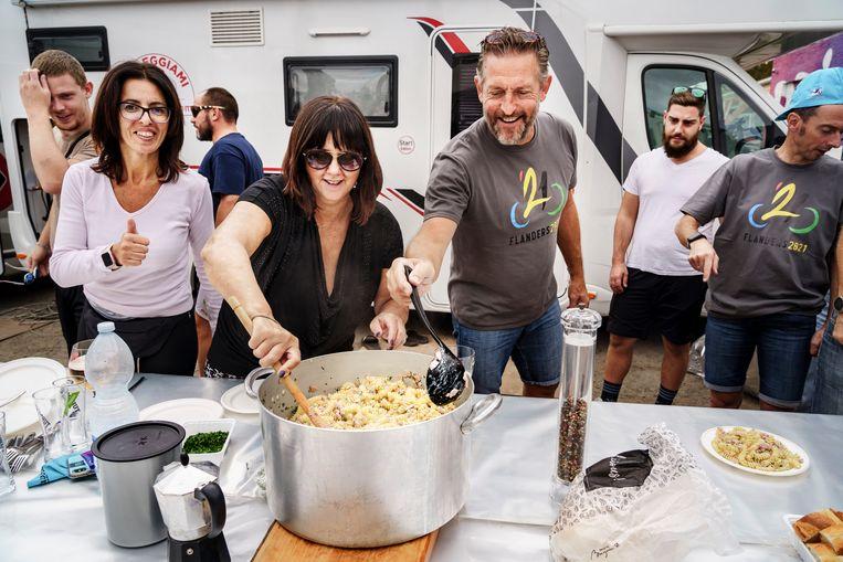 De fanclub van Stefano Zanini, inclusief de oud-wielrenner zelf, legt de laatste aan hun lunch. De Italianen zorgen voor de pasta, de Belgen voor het bier.  Beeld Eric de Mildt