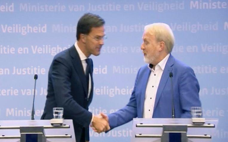10 maart: Het was nog wennen: handenschudden mag niet meer, had Rutte net verteld in de persconferentie, waarna hij Van Dissel de hand schudde Beeld AP