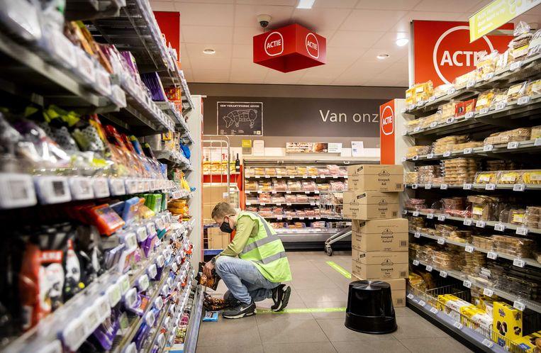 Een medewerker aan het werk in een supermarkt. Veel supermarktpersoneel krijgt er 2,5 procent salaris bij. Te weinig, volgens de vakbonden. Beeld ANP