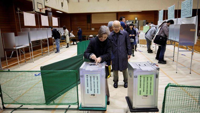 Japanse kiezers brengen hun stem uit bij een stembureau in Tokio. Beeld afp