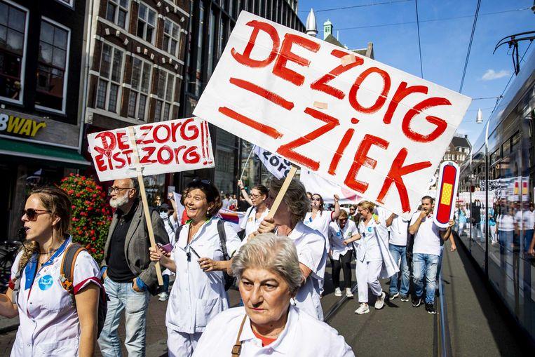 Werknemers uit de zorg hielden zaterdag een demonstratie op de Dam. Ze willen betere arbeidsvoorwaarden, lagere werkdruk en een hardere aanpak tegen agressie.  Beeld Sem van der Wal/ANP