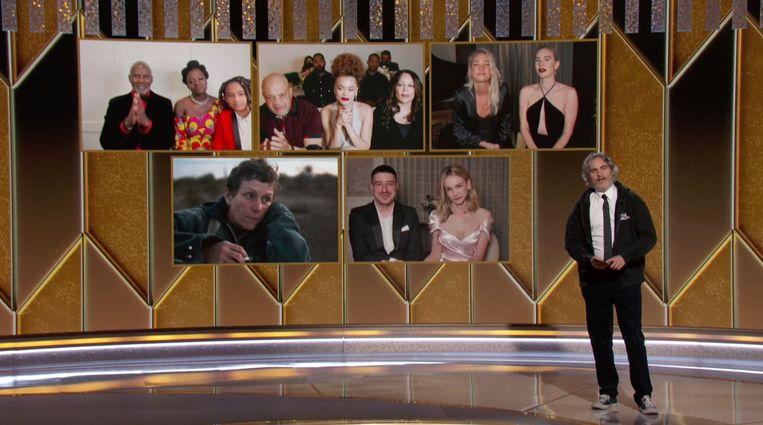 Zo zag de uitreiking van de Golden Globes er dit jaar uit: de genomineerden achter presentator Joaquin Phoenix op een scherm.  Beeld AP