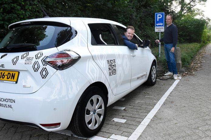 Eric Jan Hagoort (staand) en Robin Jongerius bij de standplaats in Linschoten waar de elektrische Renault Zoë vanaf vrijdag beschikbaar is als deelauto voor alle Linschotenaren.